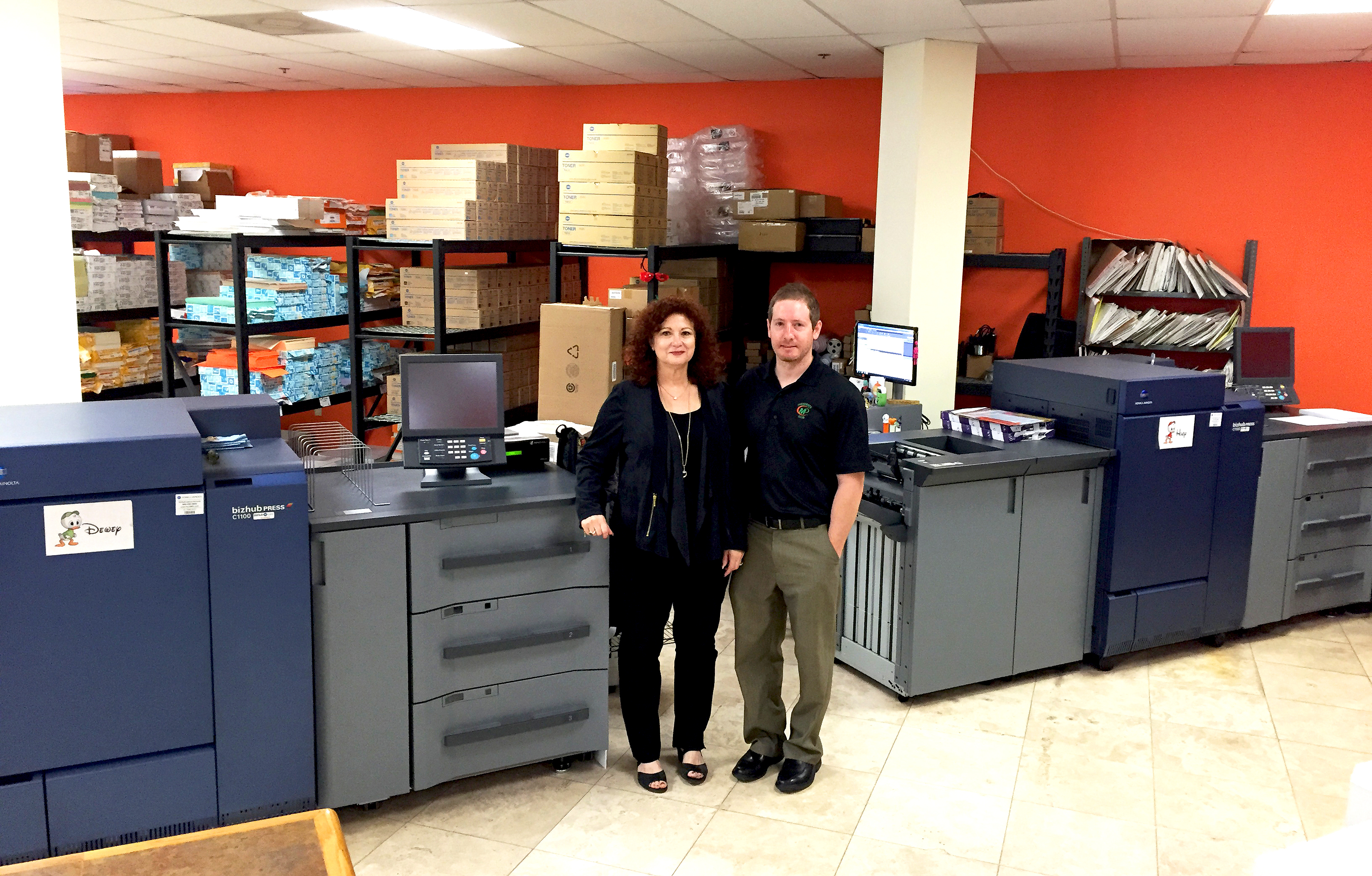 Minuteman Press franchise owner Matthew Perry (right) and his mother Gail alongside two Konica Minolta bizhub PRESS® 1100s.